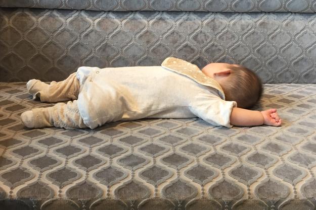 初めての寝返り成功を決めて、ソファで大の字で寝る我が子。